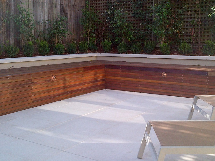 Spotted gum timber daybed incorporating low voltage garden lighting. Paving is 600x600 lightly banded sandstone.