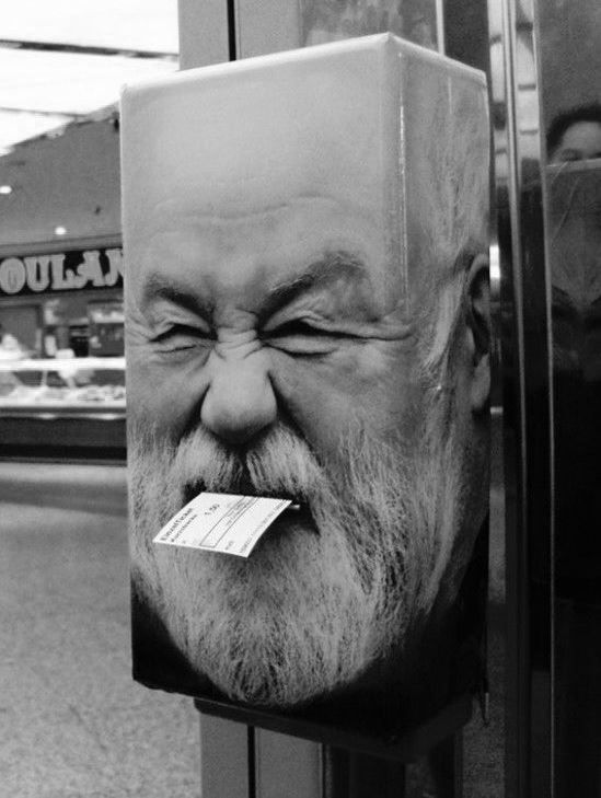 A ticket box wrapped with vinyl image of a man's face.