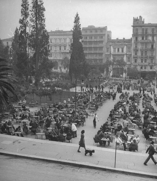 Crowds eating at busy downtown sidewalk cafe.Location:Athens, Greece Date…