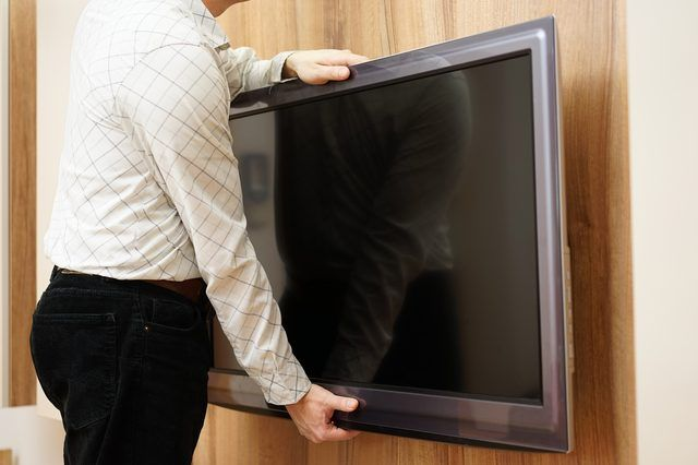 repairman gives television down from the wall in living room
