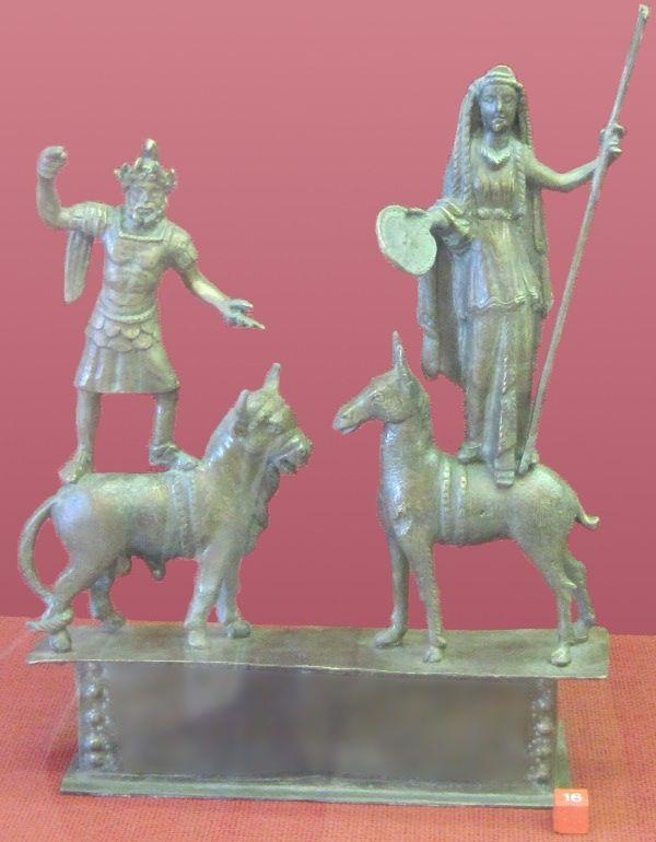 Statuette de Jupiter dolichénien (gauche) debout sur son taureau et de Junon la Reine (droite) sur sa biche. La bipenne et le foudre de Jupiter ont disparu, mais il reste toujours le sceptre et le miroir (ou bien la patère ?) de Junon. (On remarque que l'animal de Junon — identifié normalement comme une biche — se ressemble presque à une chamelle voire à une ânesse. Cependant, les sabots sont clairement fendus.) (Römisch-Germanisches Zentralmuseum, Mayence)