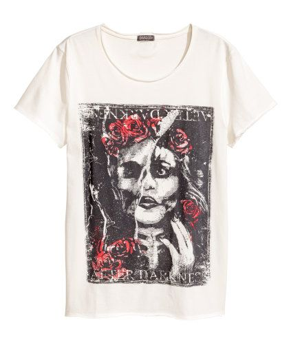Naturweiß. T-Shirt aus weichem, gewaschenem Baumwolljersey mit Frontdruck. Offene Kanten an Halsausschnitt, Ärmeln und Saum.