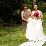 Mother holds daughter's dress as bride struggles to walk down the aisle resulting in immediate laughter. Photo by www.theweddingcentral.com