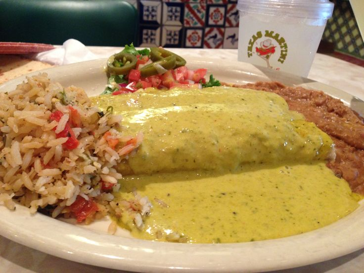 Chuy's Chicka Chicka Boom Boom Enchiladas.  Sauce is made from green chiles, tomatillos, cilantro, lime, spices and melted cheese poured over a roasted chicken enchilada served with spanish rice and refried beans.  This sauce looks/sounds absolutely delicious... would be awesome over a black bean and rice enchilada (for vegetarians).
