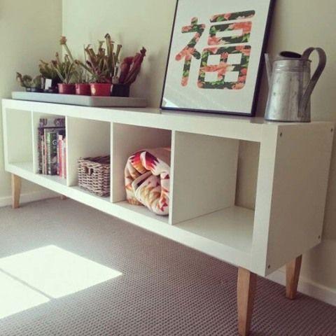 La autora de Joli Place ha renovado su Kallax de cinco cubículos, utilizada habitualmente de forma vertical a modo de librería, colocándola de forma horizontal, con patas de madera y como mesita auxiliar en un soleado lugar de paso.
