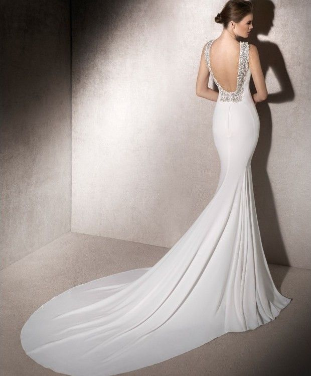 Espectacular y elegante vestido de novia confeccionado en crepé. Sensual escote por la espalda bordeado en pedrería, cola alargada y corte sirena. #vestidosdenoviaoriginales #vestidosdenovia2018 #vestidosdenovia2019 #vestidodenoviaelegante #vestidosdenoviaenmadrid #vestidosdenoviacortesirena #vestidosdenoviasexi #losmejoresvestidosdenovia