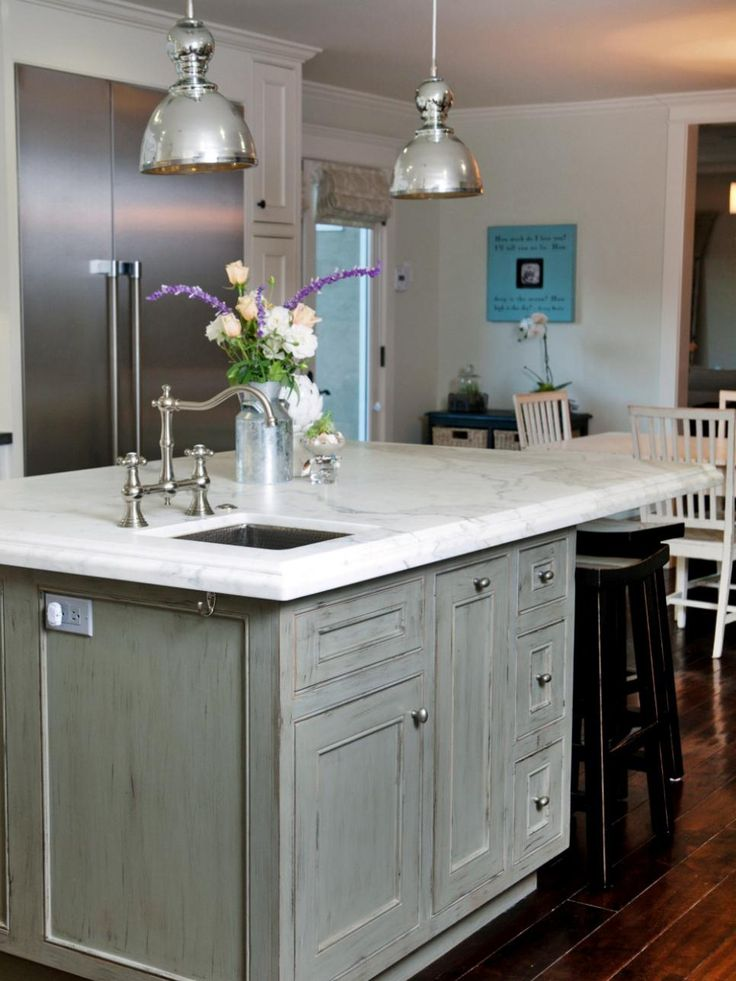 The light gray kitchen island creates a stark contrast against the dark wood flooring. The gray color palette enhances the gray-green color tones of the Calacatta marble countertop. The chrome light fixtures and hardware add shine to an otherwise casual kitchen. Design by Darci Goodman