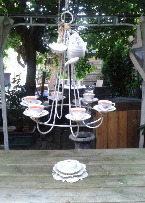 kandelaar met theekopjes en theepot met zelfgemaakte kaarsen erin.