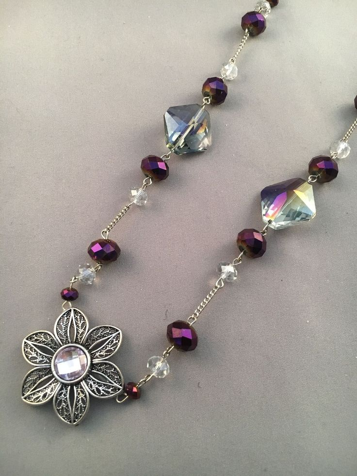 This necklace has purple beads with large smoky acrylic beads with a metal flower with a pink center pendant. #bijouterie #JewelryInspiration