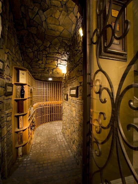 Mediterranean Wine Cellar with can lights, Built-in bookshelf, Standard height, Interlocking Pavers, Wall sconce