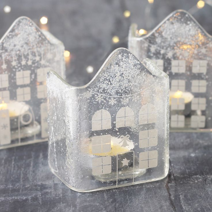 Add a little warmth and sparkle to your home this winter with these gorgeous handmade glass tea light houses. They will brighten up a window-sill or mantlepiece and create a little 'hygge' to your room.  Each house is decorated with unique designs including little windows, doors, bunting, fairy lights and Christmas trees. The glass is the sprinkled with glass snow for a lovely festive feel. When the tea light is lit the candle light will flicker and light up the house creatin...