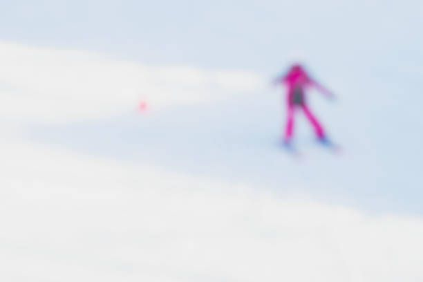 blur image of young girl learning on equipped for skiing snowy slope