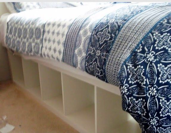 Two IKEA bookshelves laying on their sides and topped with bed slats make an instant storage bed. Leave cubbies open or find baskets, bins or tubs to add finished storage