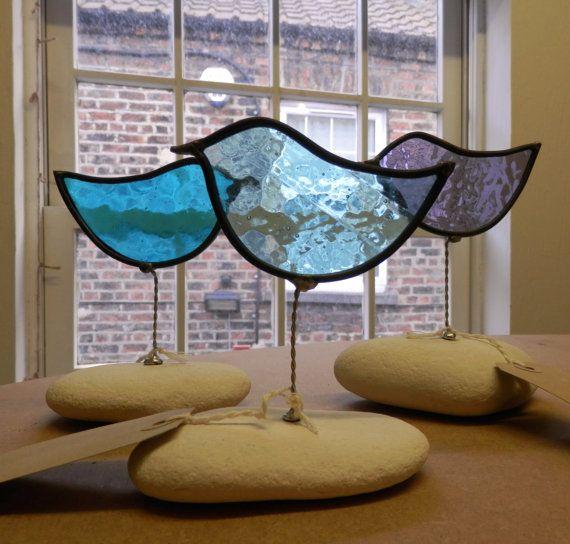 Small blue stained glass bird suncatcher on white stone