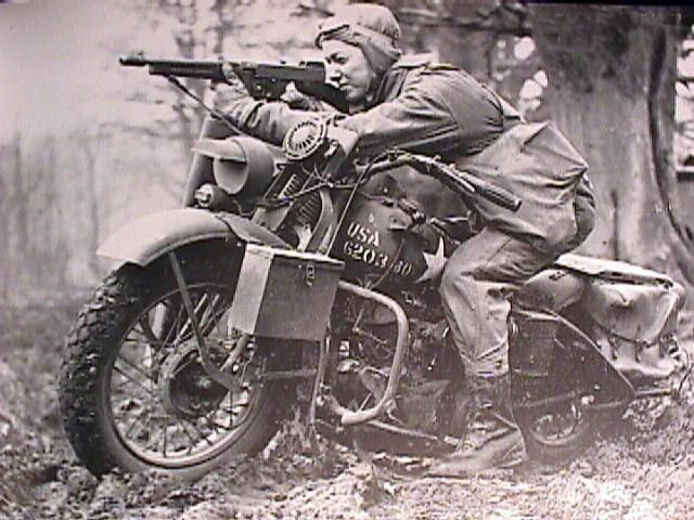 rtA US Army private on a Harley Davidson 'Liberator' shooting with his Thompson gun, uknown location, unknown date.  #WWII #History @Laura Harley-Davidson @U.S. Army