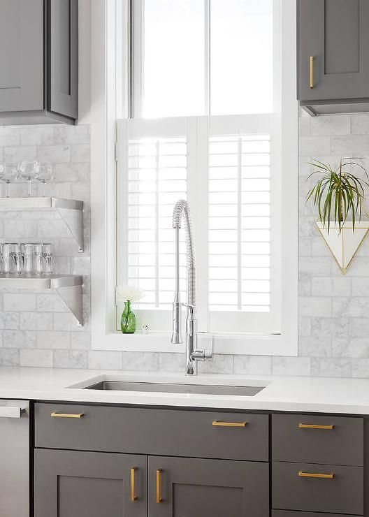 Under a window covered with plantation shutters, a stainless steel undermount sink is paired with a polished nickel pull out faucet fixed to a white quartz countertop accenting gray shaker cabinets fitted with Schoolhouse Electric Edgecliff Pulls.