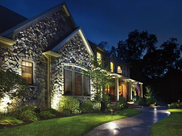 22 Landscape Lighting Ideas: Shadow can be just as interesting as light. The spotlights on the front of this house were placed very close to the foundation so that the light would catch the edges of the beautiful stonework and create an intricate shadow pattern. To avoid a dead dark spot at the peak of the roof, the designer placed one spotlight on a stem in the flower bed (at left) that sends light all the way to the top. From DIYnetwork.com