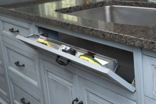 Hidden sponge storage under sink... small but usuable. This is better than having those wasted false drawer faces. My father loved this idea the first time he saw it. He was a fan of hidden storage and clever storage solutions.