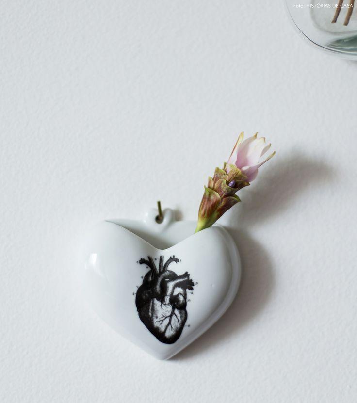 Vasinho de porcelana com flor delicada decora a parede da sala de estar.
