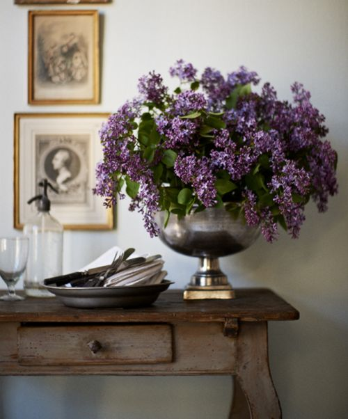 A naturally overflowing urn of lilac blooms on a rustic table- beautiful!