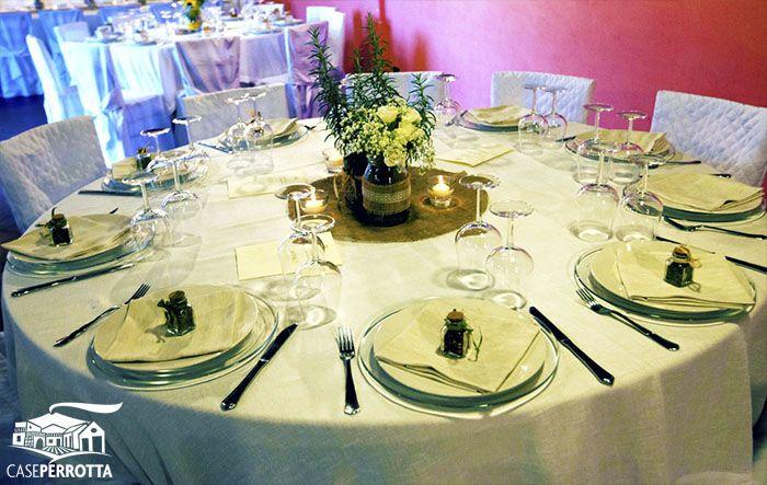Allestimento per ricevimento nozze con tavoli rotondi e centrotavola con erbe aromatiche