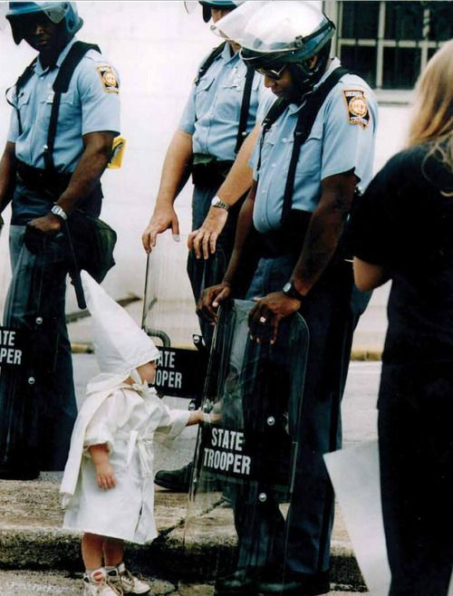 """zerodarkpervy: thegist: """"… in the 20 years since, this emotionally complex photograph of a Klan-robed toddler playfully touching the riot shield of a bemused African-American state trooper has gone uncelebrated and largely unknown."""" (Photographer: Todd Robertson, 1992)"""
