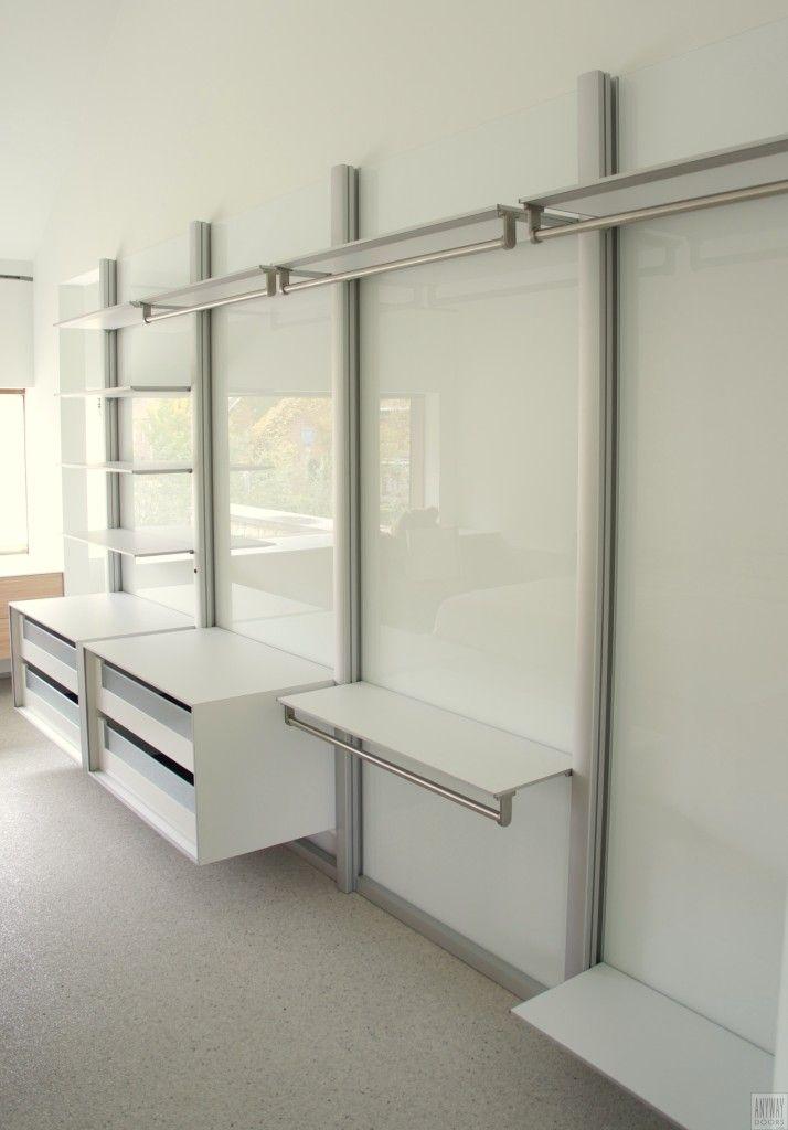 Moderne slaapkamer met inloopkast. Het modulair inloopkast systeem is met verticale aluminium profielen tegen de muur bevestigd. Tussen de profielen is de muur afgewerkt met spierwit glas om het onderhoud te vereenvoudigen en de geïntegreerde led verlichting s' avonds optimaal te benutten. http://dressaway.com