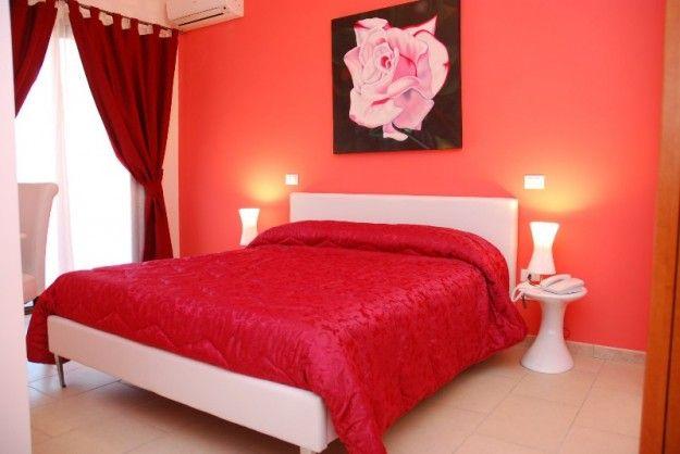 Colori caldi per la camera - Pareti nelle tinte del rosso per una camera da letto romantica.