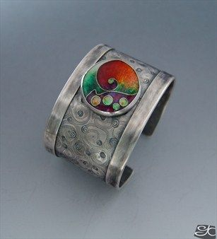 Handmade sterling silver cuff bracelet with cloisonne enamel focal piece.The silver is textured with an spiral pattern.