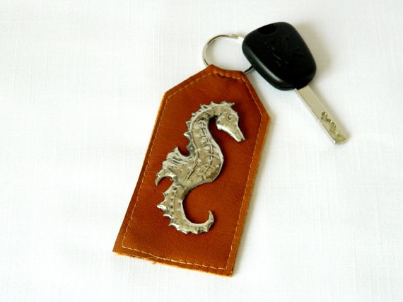 """From the Sea to your keyring ! This genuine leather keyring in a tan colour has a pewter repousse Seahorse on the front. Super gift for fathers day.     This leather keyring measures approx 12cm (4 1/2"""") (excluding ring) x 5cm ( 2"""") wide."""