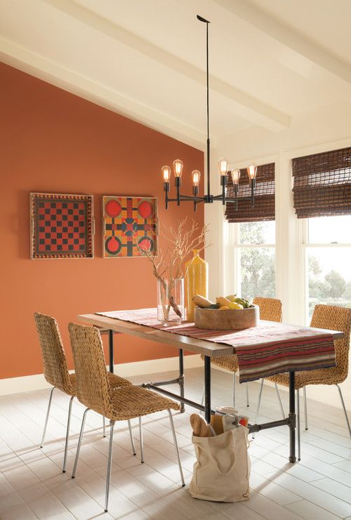 Nicely painted white ceiling with beams across with an elegant yet minimalist chandelier hanging, orange color painted wall, white painted window glass frames, rectangular brown wood dining table with nice woven design chairs around it then a ceramic tile floor.  Source: https://www.houzz.com/photo/51850354-sherwin-williams-southwestern-dining-room-columbus
