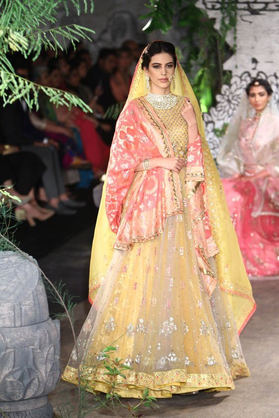 Dupatta draping ideas for Indian brides | Stunning bridal dupattas | Yellow net lehenga with peach orange silk dupatta | Double dupatta draping ideas | Anuj Modi | Indian bridal fashion | Bridal couture | Bridal look inspiration | Every Indian bride's Fav. Wedding E-magazine to read. Here for any marriage advice you need | www.wittyvows.com shares things no one tells brides, covers real weddings, ideas, inspirations, design trends and the right vendors, candid photographers etc.