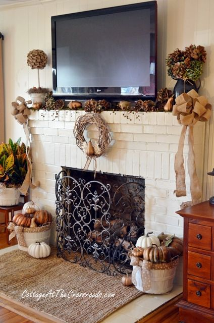 Elegant fall mantel. Black vases with fall-colored hydrangeas. Basket filled with pumpkins with burlap bow.