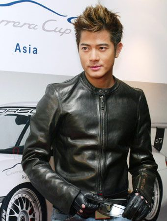 Hong Kong singer-actor Aaron Kwok poses in front of a poster for the Porsche 911 GT3 at a news conference in Hong Kong January 28, 2003.