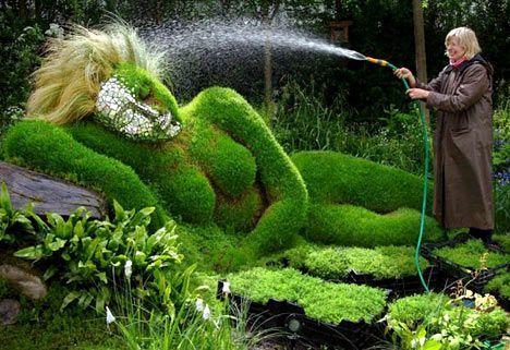 Exposición en la entrada del jardín de flores de Chelsea;  exposición , de una escultura  mujer  de barro y pasto  reclinada sobre cabecera  de pasto. Hecha por Sue y Peter Hill