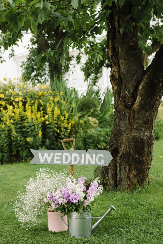 watering cans filled with wild flowers & wooden wedding direction sign - Image by Caroline Hancox Photography - A lace fishtail Justin Alexander wedding dress with pastel colour scheme including a pink peony bouquet for a marquee with ice cream van