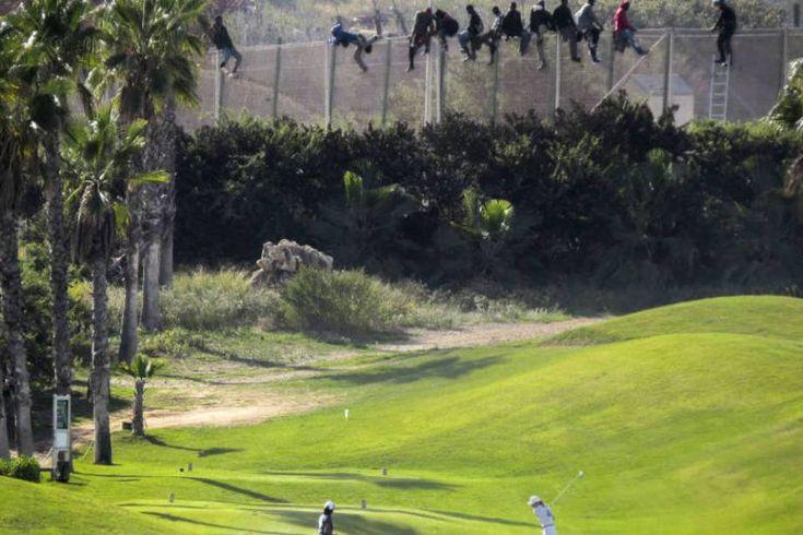 """Uma crise sem precedentes. Golfistas observam refugiados africanos que tentavam pular a cerca entre o enclave espanhol de Melilha e o Marrocos. Para a Anistia Internacional, a mobilização dos líderes globais para lidar com este problema é """"um vergonhoso fracasso"""".  Fotografia: Jose Palazon / Reuters.  http://exame.abril.com.br/mundo/17-fotos-emocionantes-de-refugiados-chegando-a-europa/?ocid=sp"""
