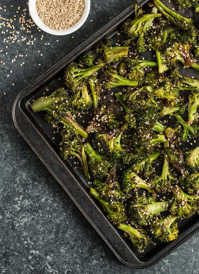 Roasted broccoli is a dinner staple in our household. It's one of the easiest ways to get some greens on our plates — especially on those nights when our dinner timeline is particularly tight. I can grab a bag or two of frozen broccoli and we can eat as we normally do, but with a fraction of the prep. Since we eat it so regularly, I've tried plenty of variations on roasted broccoli. To date, this sesame-ginger roasted broccoli is my family's favorite. Loaded with flavor, it's still versatile…