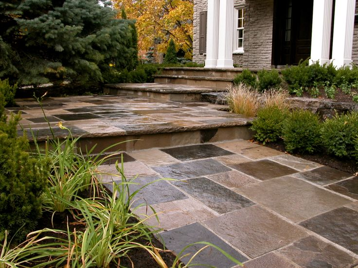 BCH Landscaping Design and Contracting Square-cut Wiarton flagstone on front porch and steps with an Armour stone boulder retaining wall