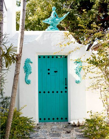 In a Miami house, the bold tropical colors start at the Moroccan-style front door, painted Benjamin Moore's Cayman Lagoon. The boy on the dolphin sculpture and the seahorse reliefs are made by Denmark Art Stone from original 1940s molds and painted Benjamin Moore's Green Sponge. photog: Mikkel Vang, housebeautiful.com