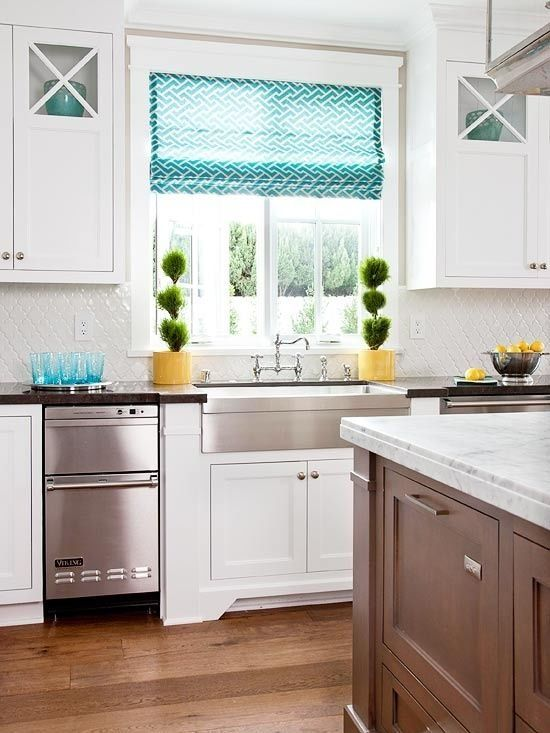 White kitchen with large window above sink.  Note the full length marble sill and the window treatment size.