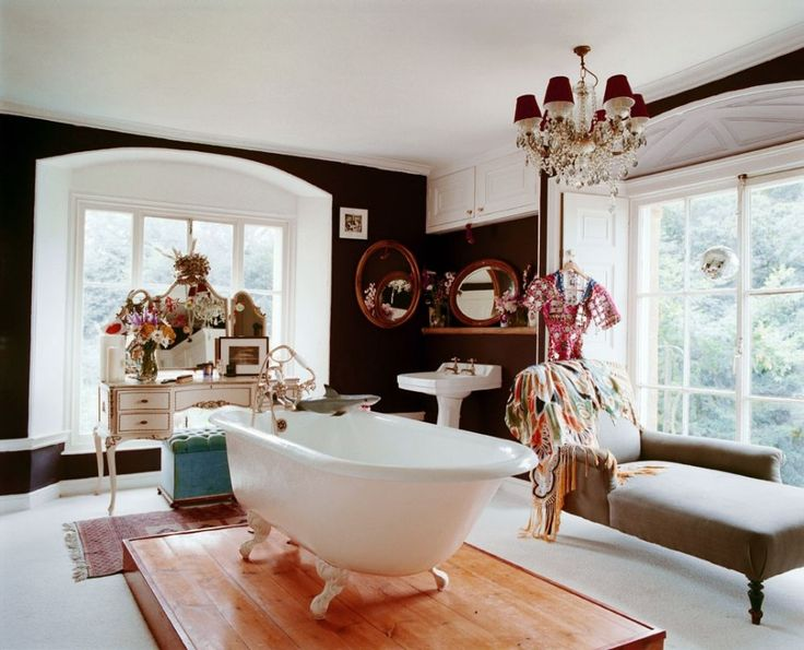 A freestanding Victorian bathtub rests on a wooden base in the center of the master bathroom at Cricket Court—Alice Temperley's Somerset Country Estate