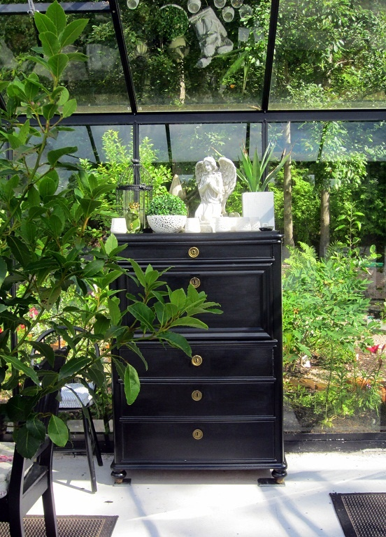 We painted an old dresser black and placed it in the greenhouse for storing garden tools.