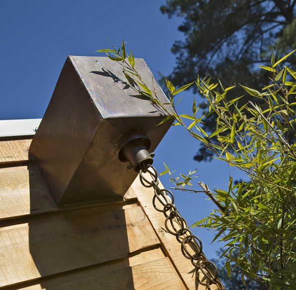Rain chains can beautifully take the rainwater from the roof and direct it down to reflecting pools, planters, and storm water run-off reservoirs for irrigation, and these systems can be DIY with materials as simple as binder rings, wire rope, and some planters or recycled barrels.