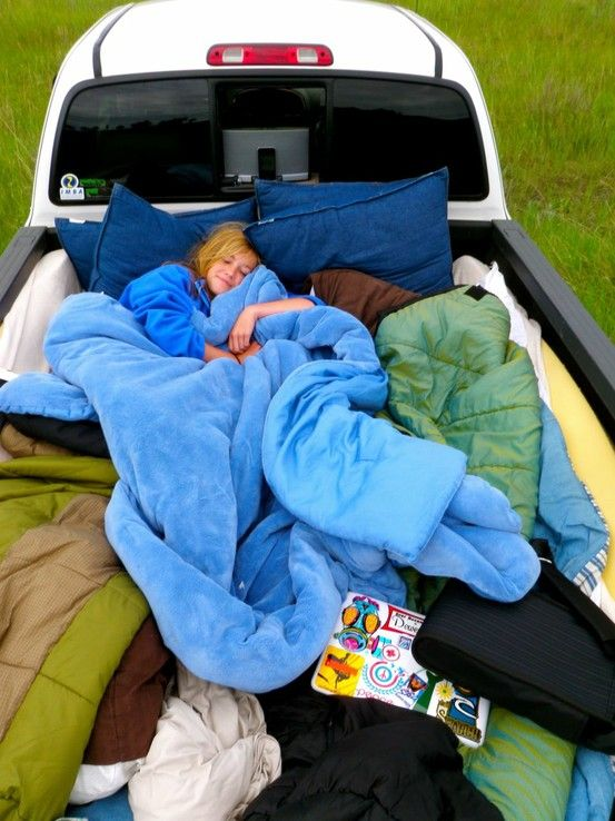 Air mattress, lots of blankets and lots of pillows all bundled up in the back of a truck for a camp out under the stars . Have to try this!