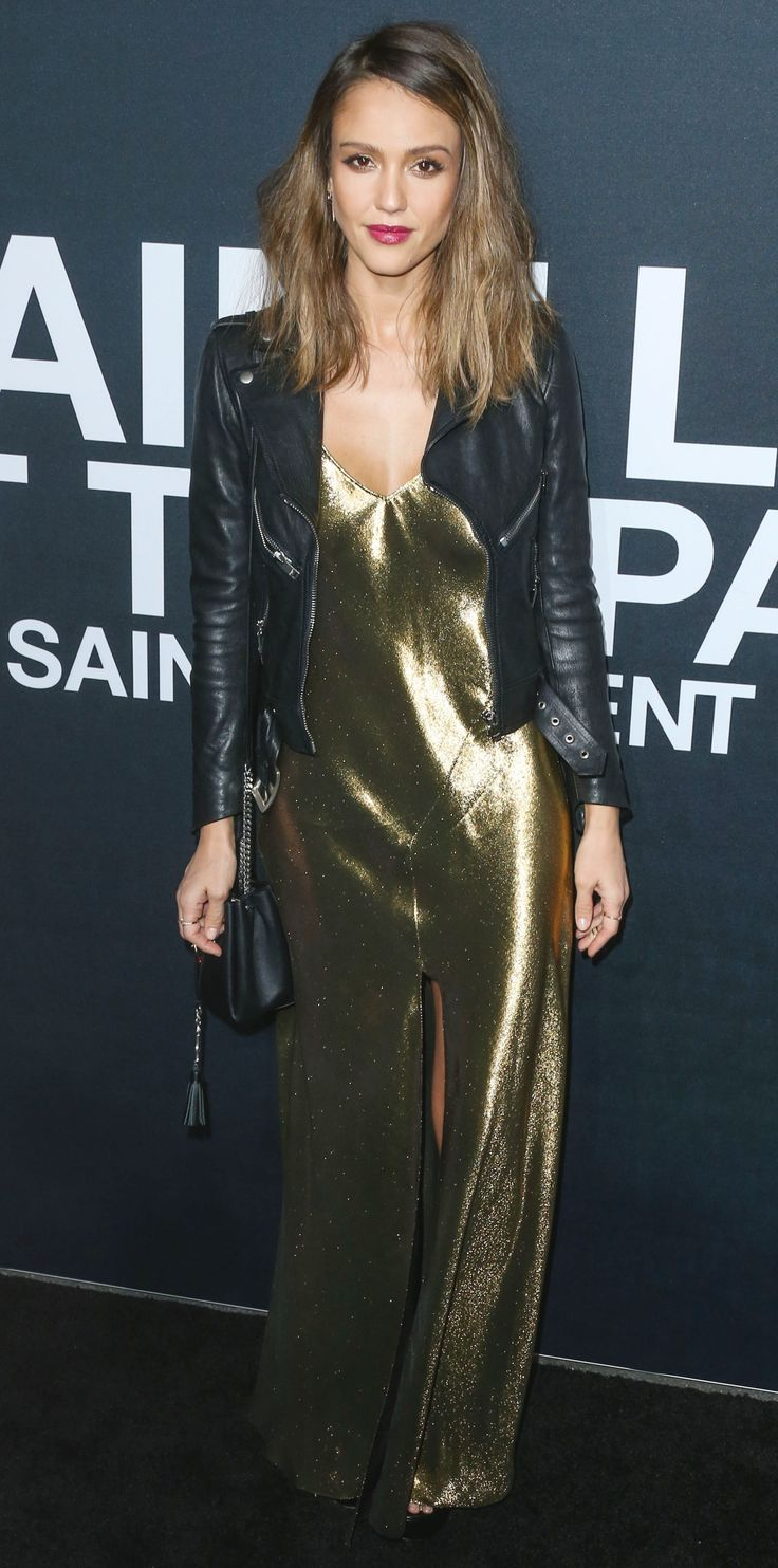 Jessica Alba went glam rock for the Saint Laurent show in a liquid metallic gold Saint Lauren slip dress that she toughened up with a black moto jacket, a chain-link purse, and strappy platforms.