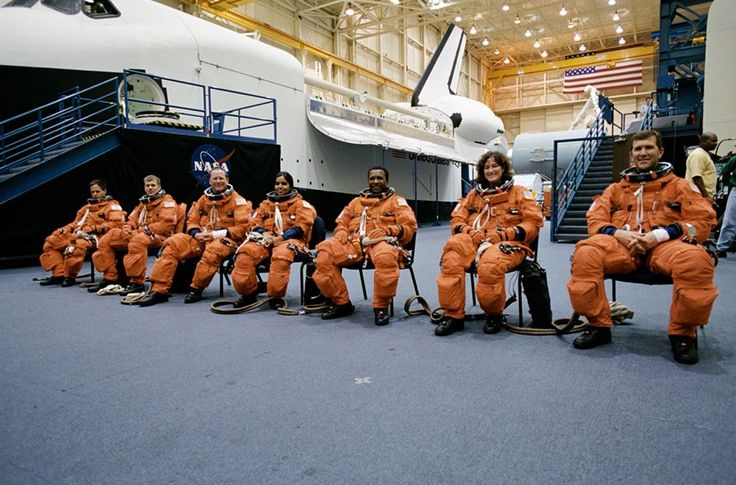 Shuttle Columbia STS-107 crew members posing for photo at the Space Vehicle Mockup Facility (SVMF). From the left are Ilan Ramon, Payload Specialist; William C. McCool, Pilot; along with David M. Brown and Kalpana Chawla, both Mission Specialists (MS); Michael P. Anderson, Payload Commander; Laurel B. Clark, MS; and Rick D. Husband, Mission Commander. NASA Identifier: JSC2001-02464.