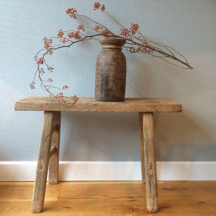 Oud houten bankje, houten kruik, rozenbottel takken. Grijs muur