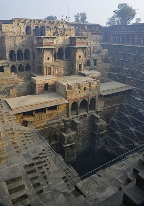 """Chand Baori is a famous stepwell situated in the village Abhaneri near Jaipur in Indian state of Rajasthan. This step well is located opposite Harshat Mata Temple and is one of the deepest and largest step wells in India. It was built in 9th century and has 3500 narrow steps and 13 stories and is 100 feet deep. It is a fine example of the architectural excellence prevalent in the past.    (via 500px / Photo """"Step Well in India"""" by Joe Routon) #india"""