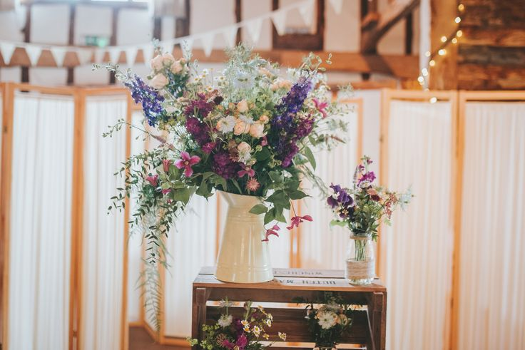 Large rustic jug arrangement for The Clock Barn  wedding ceremony.  Flowers created by Eden Blooms Florist from Blue Nigella, Purple Larkspurs, Clematis, Tanacetum Daisy, Bombastic Spray Rose, Pale Blue Delphinium & Asparagus Fern.  Image by www.tomhalliday.com
